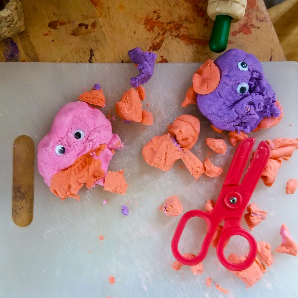 My toddler couldn't be happier to use scissors and googly eyes to create his own playdough creatures.