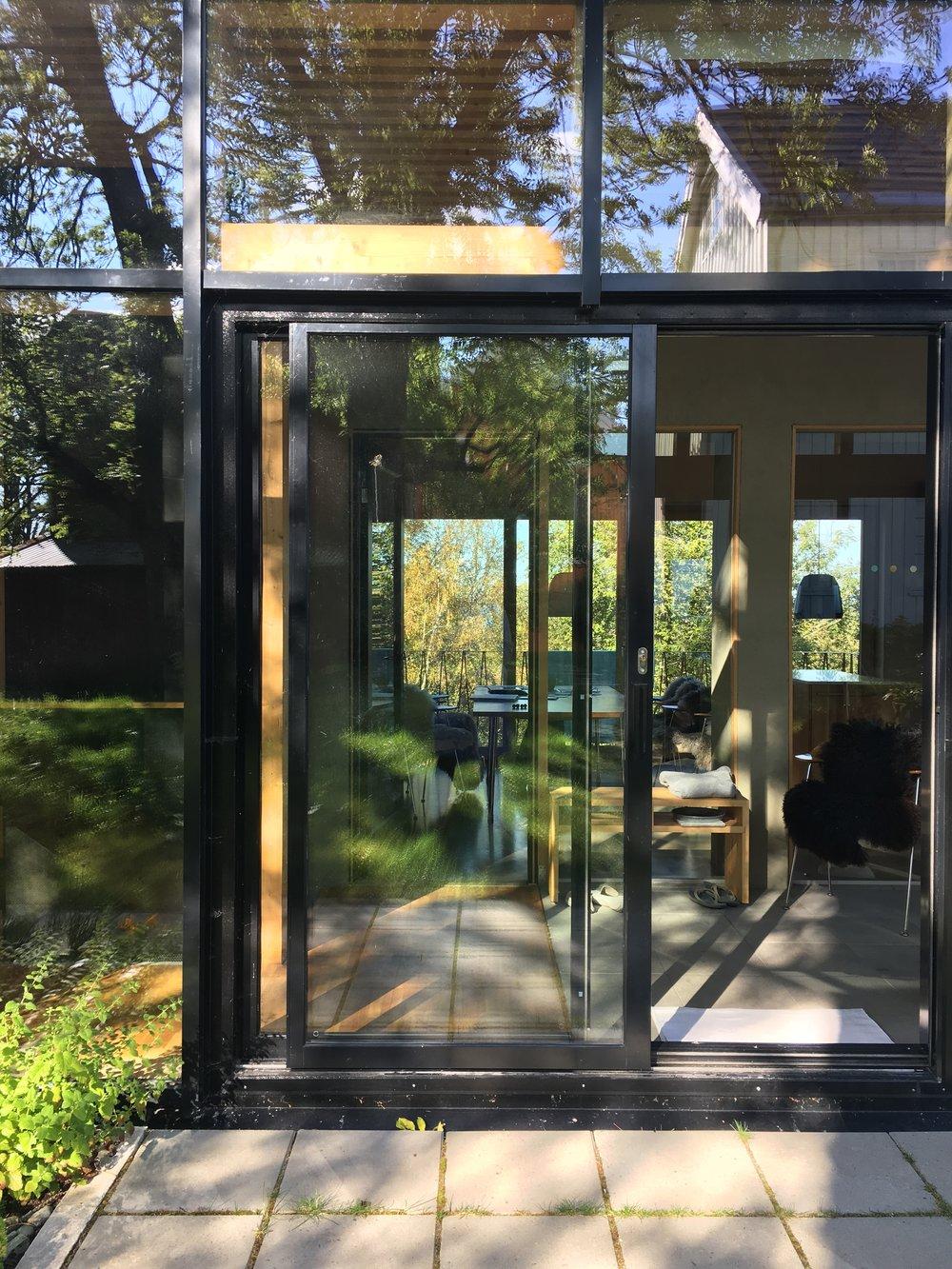 Den kvite Trønder-låna speiler seg sammen med aske-trærne i fasaden.