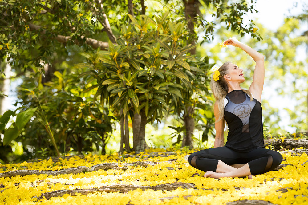 Stency Wegman transitioning to Baddha Konasana A in a field of flowers