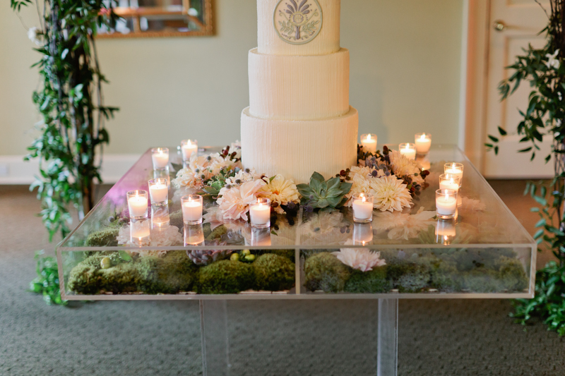 clear table with moss, votives, cake table, acrylic clear table