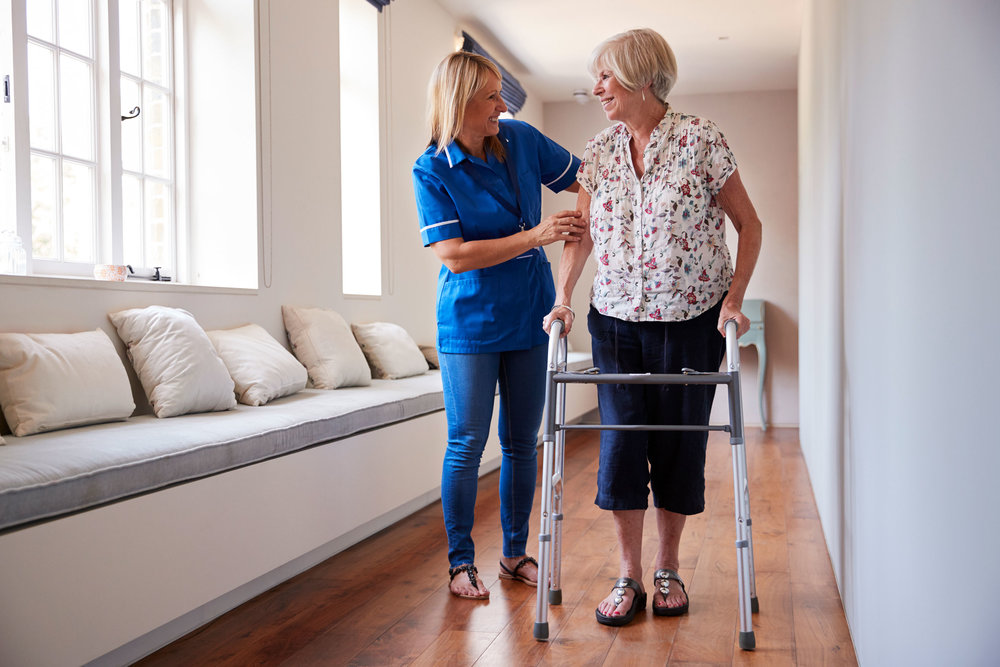nurse-helping-senior-woman-use-a-walking-frame-PNS5UFW.jpg