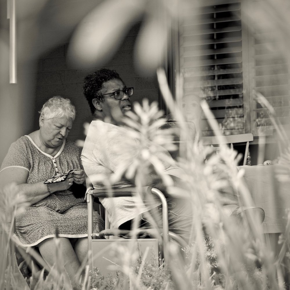 Mrs. and Mrs. Stewkis is a candid portrait of a married, same-sex interracial couple enjoying their relaxed domesticity, viewed through a screen of spring time desert blooms. The ACLU has been at the forefront of the battle for both racial equality and marriage equality.  Title: Mrs. and Mrs. Stewkis  Medium: Chromogenic Print  Size: 20 x 20 framed  Year of Creation: 2018  Price $300  For sales inquiries, please contact Etherton Gallery  www.ethertongallery.com