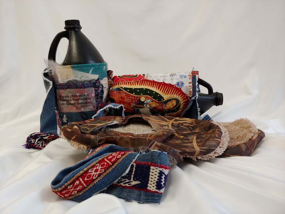 Migrants crossing the U.S.-Mexico border face many challenges including the ability to carry enough water for the journey. This work is made from new and found objects at the border, including bottles, carpet shoes (to hide footprints), a prayer book, and a lost handwritten journal of poetry.  Title: The Weight of Water  Medium: 3-D Mixed media on textiles  Size: 20 x 20 x 12''  Year of Creation: 2018  Price $950  For sales inquiries, please contact Etherton Gallery  www.ethertongallery.com