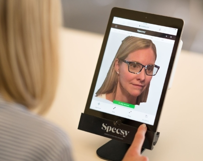 1. Customers engage with the Specsy AR app - The Specsy augmented reality app enables customers to design a sample of their custom frames on a live video feed of their face, right from the comfort of your store.