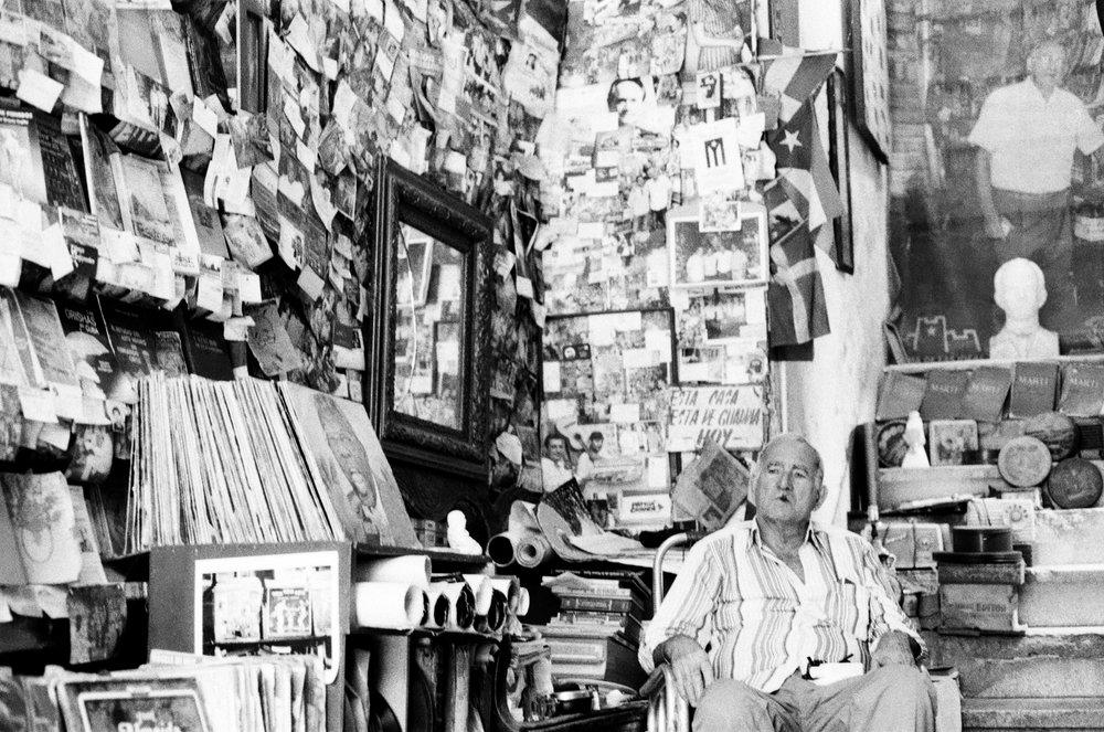 """Dans la librairie """"La Escalera"""", le propriétaire passe ses journées à attendre calmement la visite de cubains et d'étrangers, fumant son cigare à côtés de nombreux livres du Che et de vinyles des musiques d'époque."""