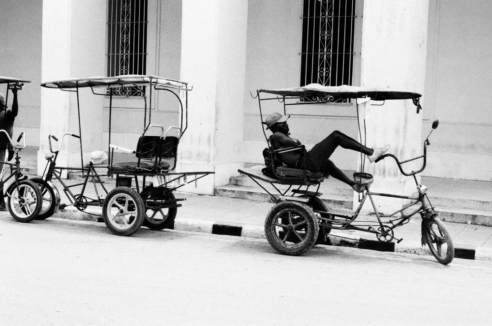 Petite pause pour un conducteur de taxi, le moteur en moins pour avancer dans les rues de Camagüey.