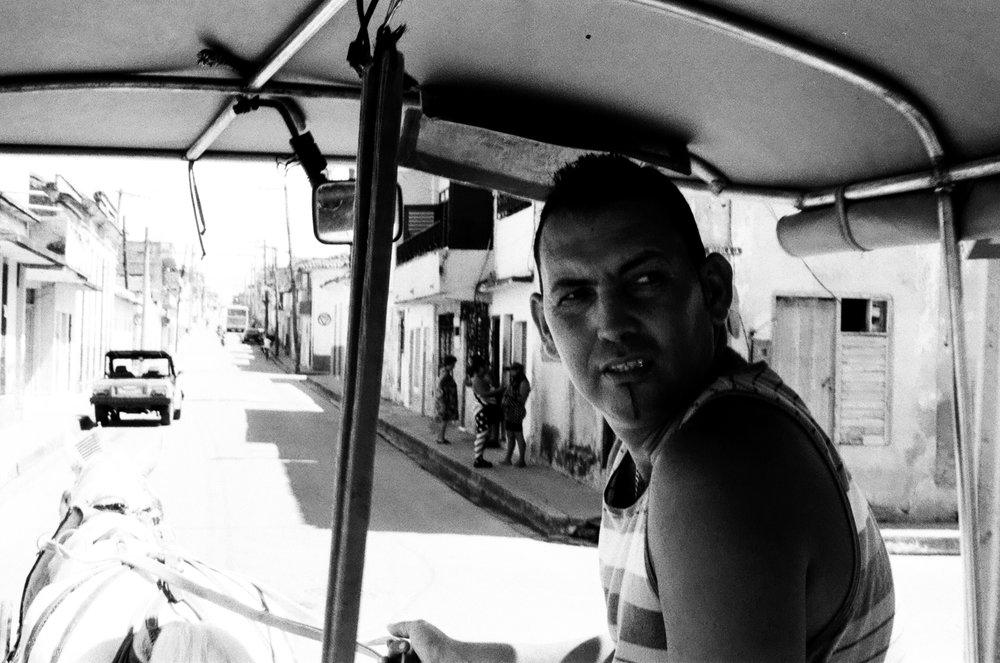 """Eladio avec son cheval Moro à Santa Clara, ville emblématique de Che guevara lors de la révolution castriste. Moro arbore sur son museau un drapeau américain aux côtés du drapeau cubain, signe d'un espoir pour Eladio de voir se réconcilier les deux """"frères ennemis""""."""