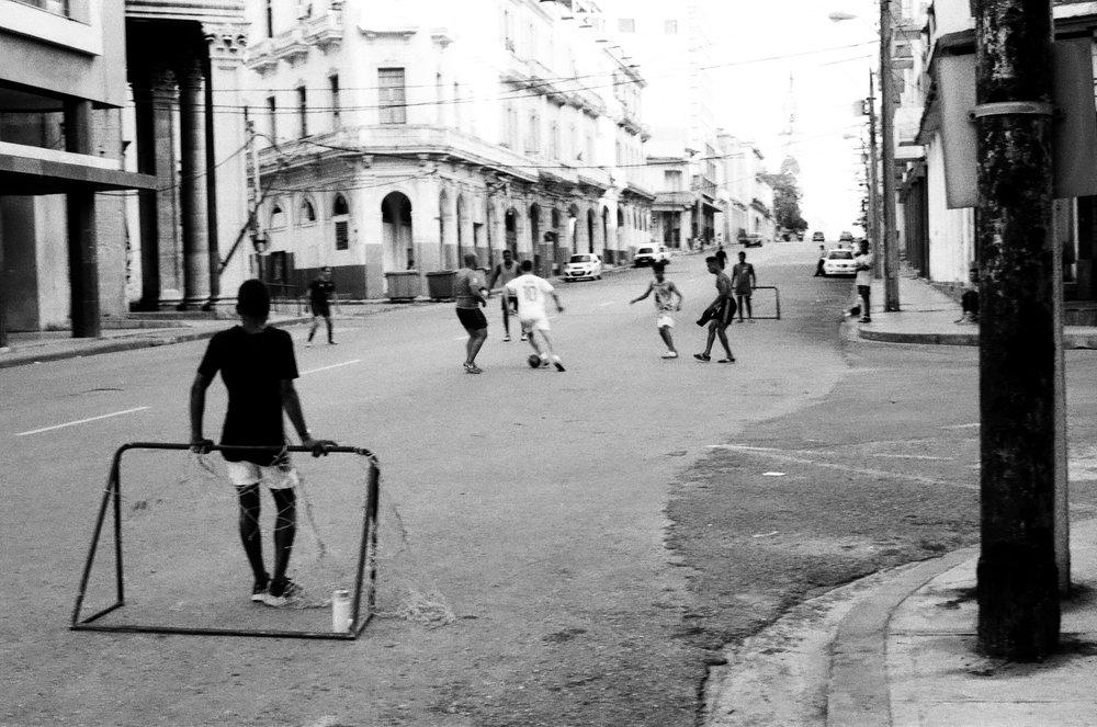 Partie de football improvisée en plein milieu d'une route principale de La Havane, sous le regard amusé de deux policiers dans le fond de l'image.