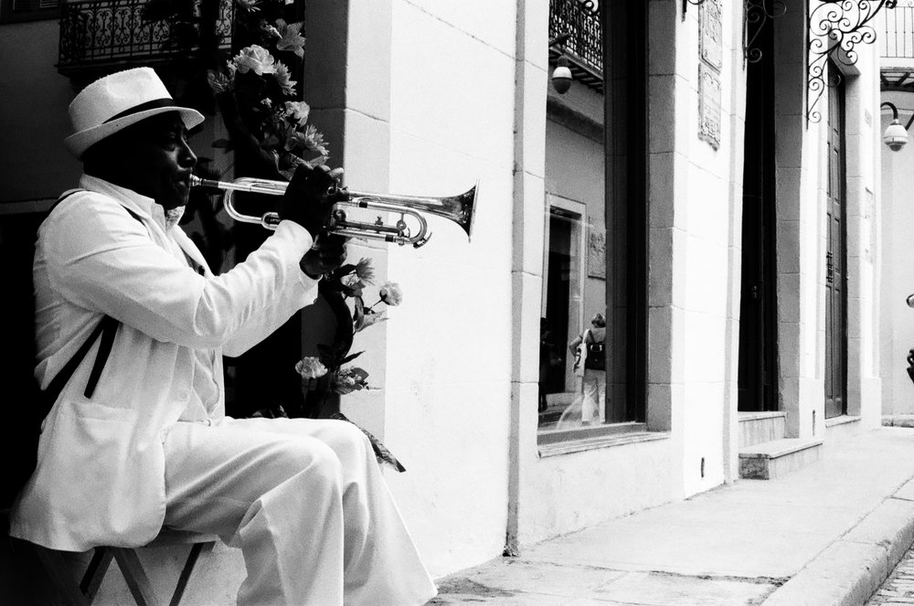 Dans les rues de Habana Vieja, un cubain élégant joue des airs de jazz à l'aide de sa trompette.