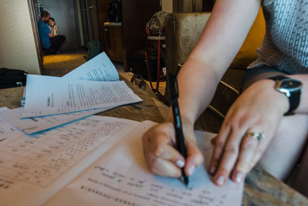 In their hotel in Nanchang a facilitator has more paperwork for the family to compete and sign. Cory comforts an inconsolable Victoria.
