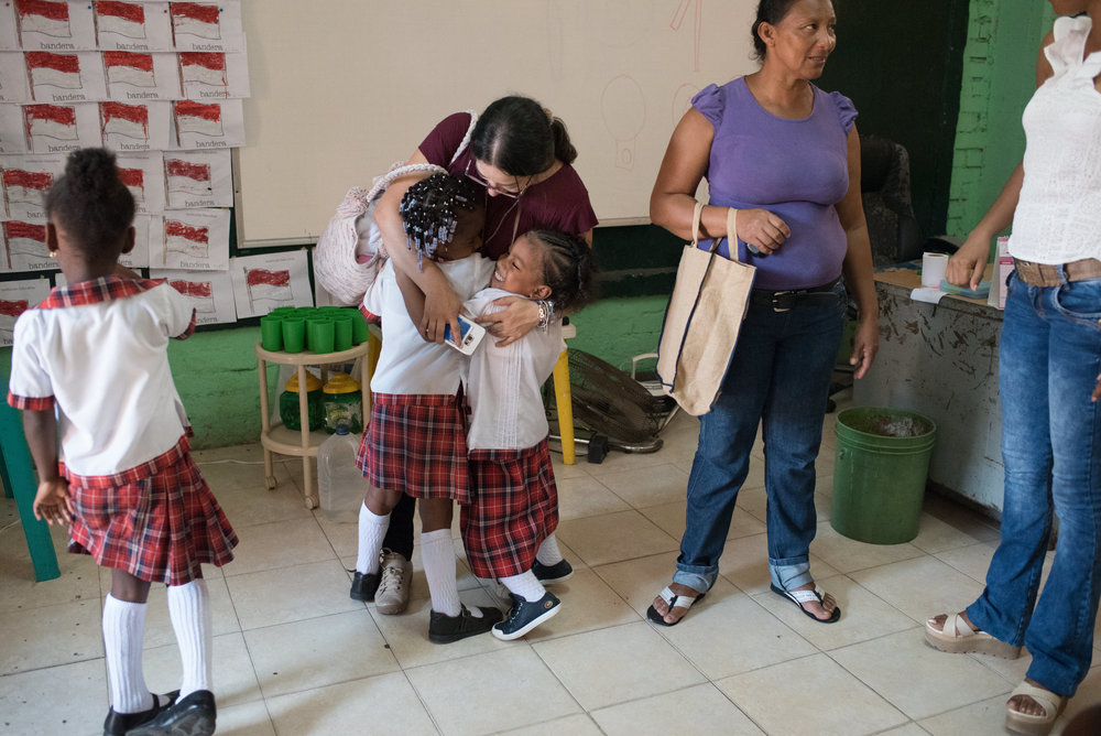 Ebony and her friend hug the social worker on Ebony's first day at the John F. Kennedy School in Buenaventura.