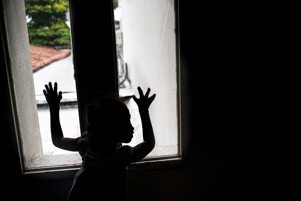 Ebony looks out the window, visible is her left hand where all the fingers have been made. Her right hand, will soon have another surgery, to separate the ring finger from the pinky.