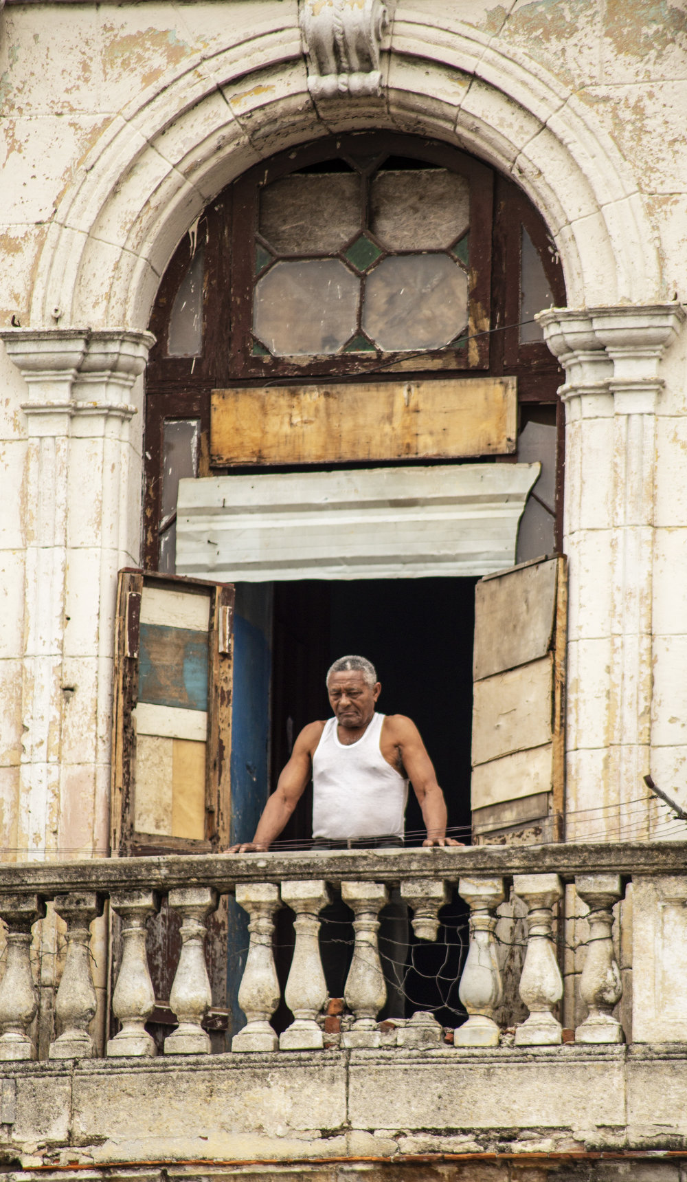 Man on the Balcony  - The photo was taken in Havana. The balcony is a glimpse of how opulent this building might have been...