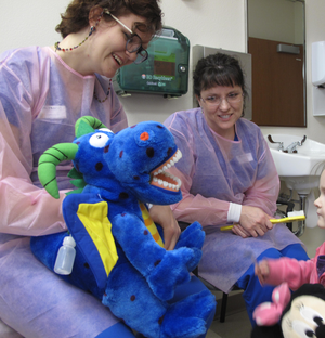 Volunteer dental practitioners conduct oral health education activities with children participants in pilot program