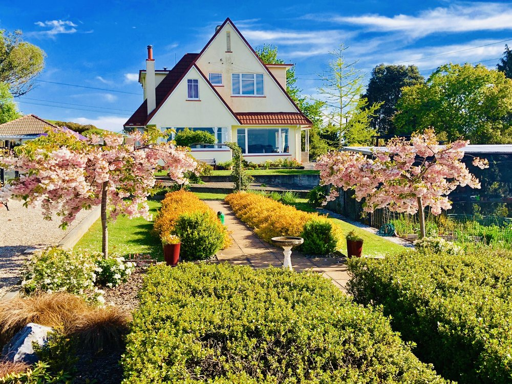 The home is beautifully designed with lush gardens, established trees, and incredible rural and mountain views.