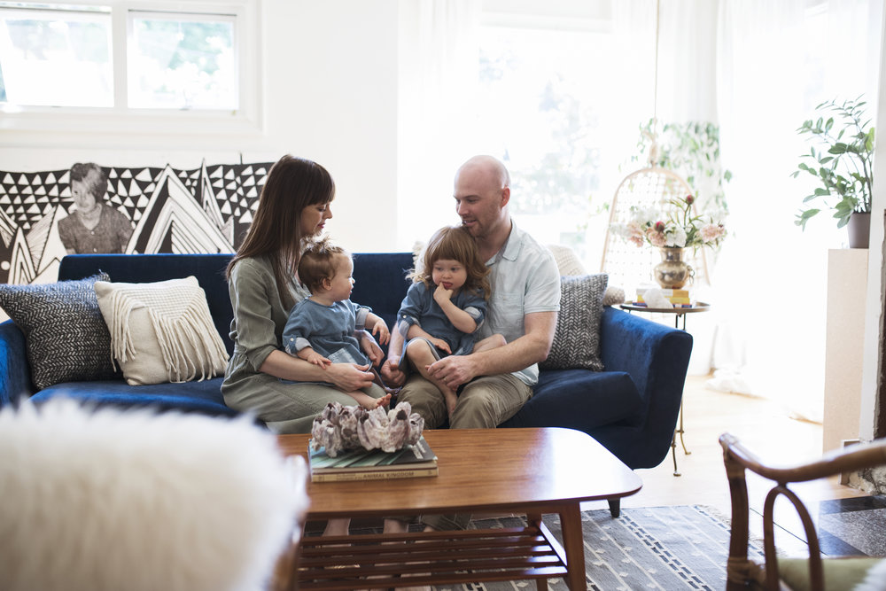 Seattle Lifestyle photographer family of four sits on blue couch at home