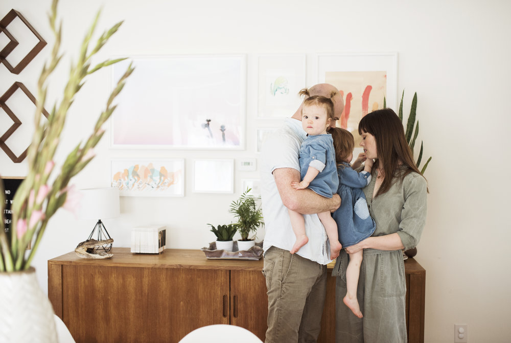 Seattle family photographer family of four standing by art wall
