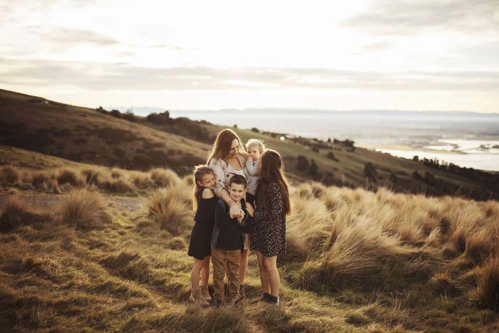 Lifestyle Photographer Mom and children on a hill at sunset