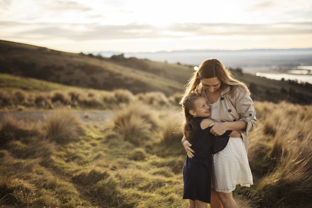 Seattle Family Photographer Mom and daughter cuddle on hill at sunset