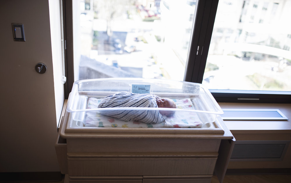 Seattle newborn photographer baby lies in bassinet in hospital