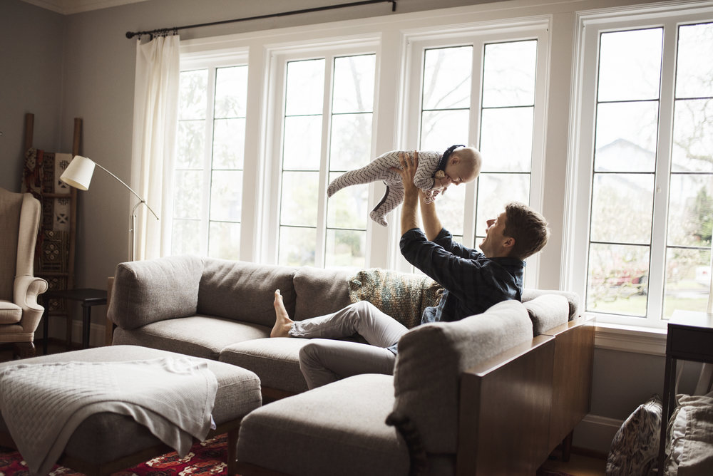 Seattle family photography dad is flying baby above his head in living room