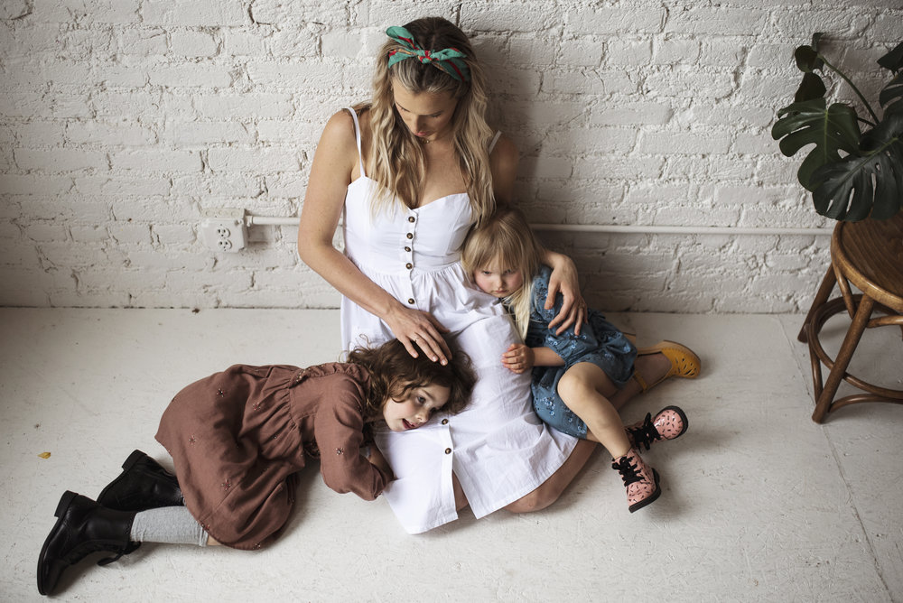 Seattle lifestyle photographer mom and daughters sitting on floor against white wall