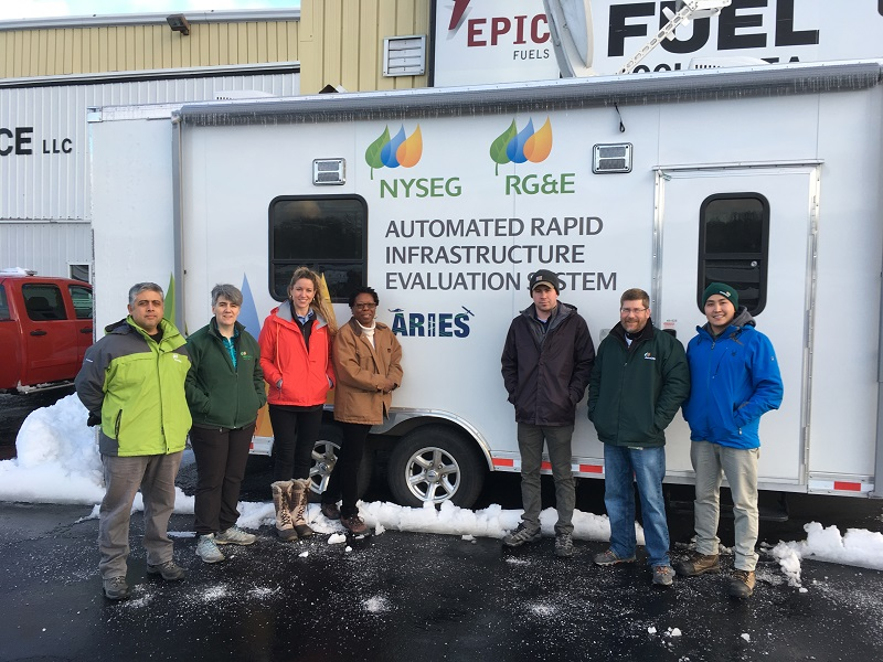 The team stands in front of the ARIES I trailer, stationed at Danbury Municipal Airport, Executive Air Services (FBO). (l-r) Marco Antonio Mendez Gonzalez, Inmaculada Sanz Santidrian, Nuria Cortes Moradell, La Wanda Ervin, Kevin Cox, Tom Evans, and Jakshylyk Urmatbek.