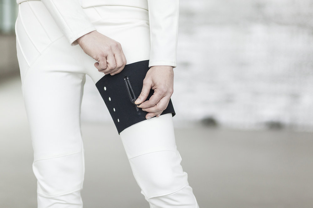 For safety reasons, pockets cannot be integrated directly into the garment. Here, a removable neoprene pocket secures to the leg.