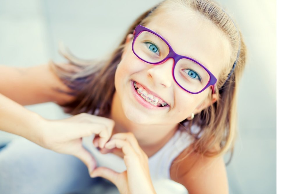 smiling-little-girl-with-dental-braces-and-glasses-showing-heart-with-picture-id842727584.jpg