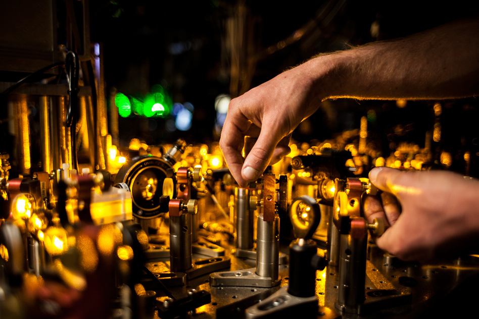 Photo of hands turning magnifying glasses and dials in a laser lab, by Jose-Luis Olivares/MIT News