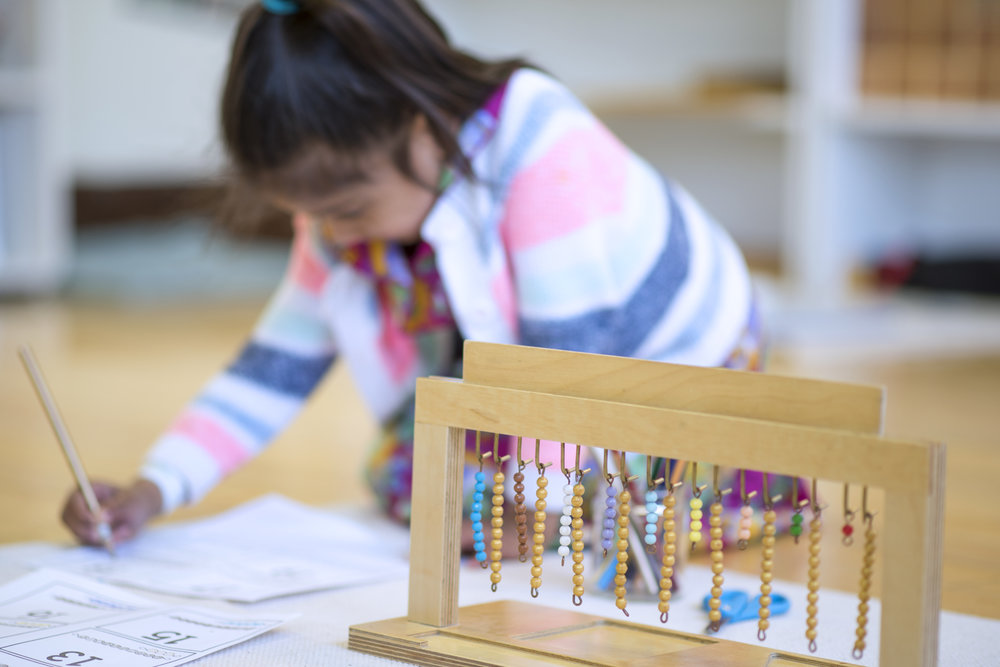 girl slightly out of focus in the background drawing with a colorful abacus in focus in the foreground