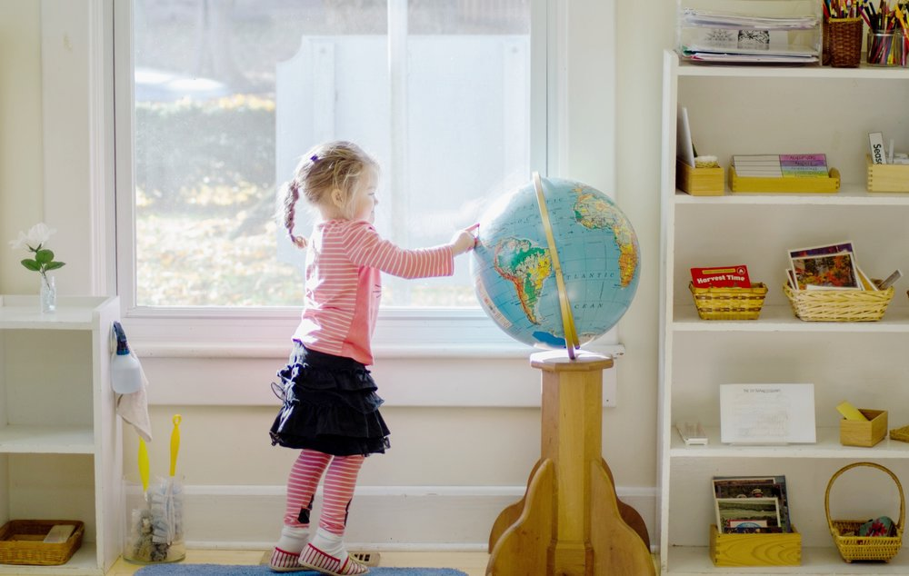little girl touching the globe in the window light of a classroom