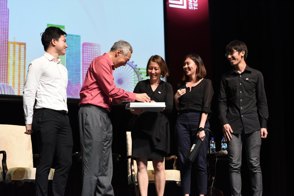 Miho Mazereeuw, Delane Foo Wei En and Kenneth Teo Liguang presenting token to Prime Minister Lee Hsien Loong