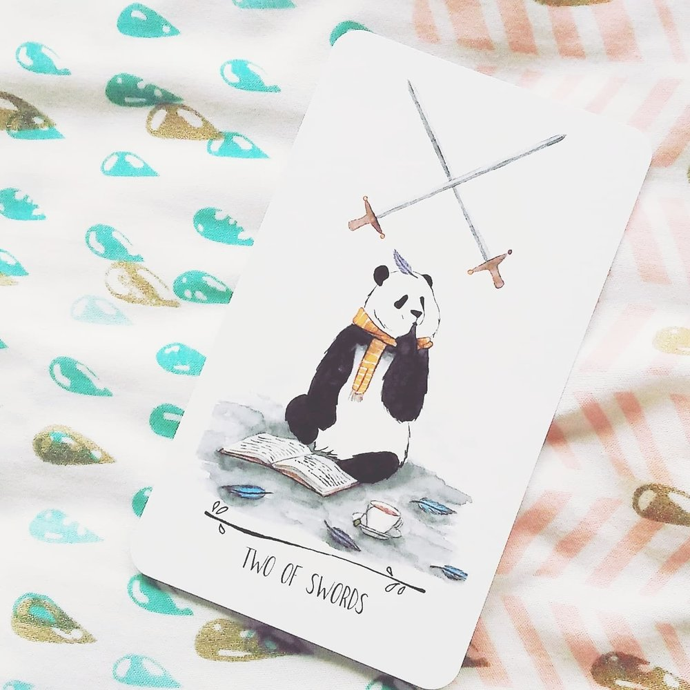 The Air Pandas (Suit of Swords) are the nerdy pandas! They are introspective, reflective, philosophical and love a good debate. They're not as drama-prone as the typical swords energy, but they have their fair share of arguments. In the 2 of Swords, the panda is contemplating over conflicting ideas over a cup of tea.