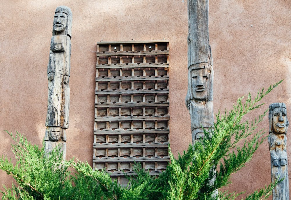 Two wooden totem poles stand on the property where Alchemy of Spirit retreat took place in Taos, New Mexico