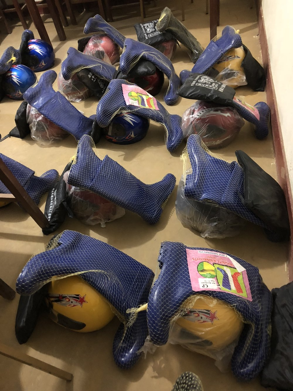 Bundles of boots, motor cycle helmets and rain jackets for our survey team. Each person  takes a bundle, which gives them vital supplies they need during the duration of the survey work.