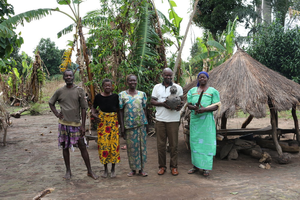 """I saw a beautiful carving of a pregnant woman by this home. My colleague Jean Bosco (second from the right) asked them to tell us the story of the statuette, which he's holding in this photo. She's actually a water container. While many traditional water containers have now been replaced by plastic jerry cans, this family keeps their """"little water lady"""" and were graciously delighted to let us meet her."""