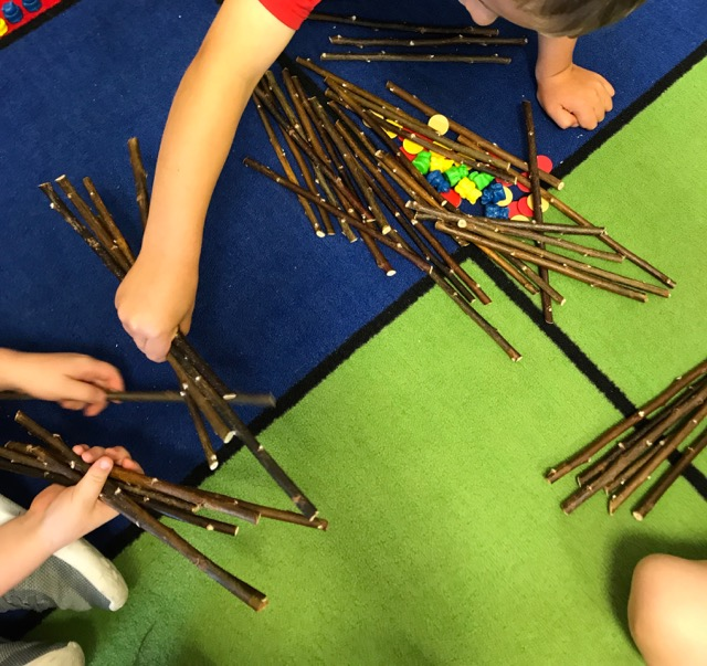 Three friends wanted to divide all the sticks evenly.  They made a big pile in the middle and are counting the sticks out, one by one, to make three equal piles.