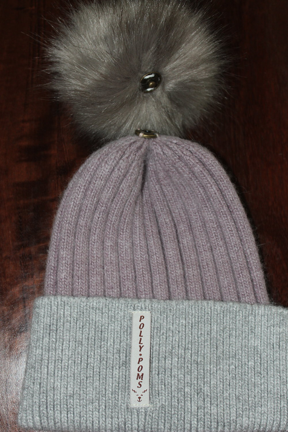 - Polly Poms are machine washable.Wash in a cold cycle, dry on low heat.Detach pom before washing.Polly Pom two toned and solid color hats are super soft, made from an Angora wool blend.Polly Pom cable knit hats are super soft made from a mix of wool and acrylic materials.Polly Pom beanie hats are super soft made from a wool blend.ALL POMS ARE FAUX FUR.