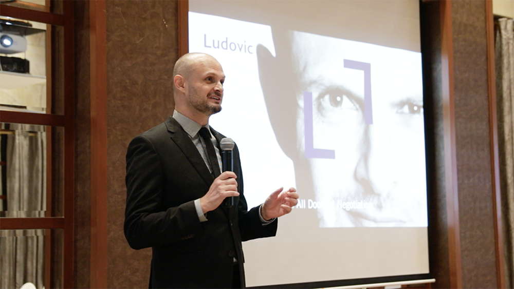 Ludovic Tendron on stage giving a speech on negotiation