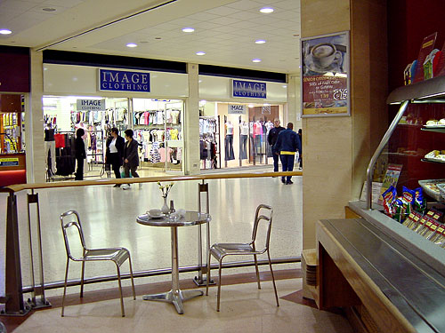 A typical shopping centre with bright lighting, I've colour corrected the image but the slight green tint from the lighting is still visible. Notice the multiple shadows under the chairs which come from multiple light fixtures.