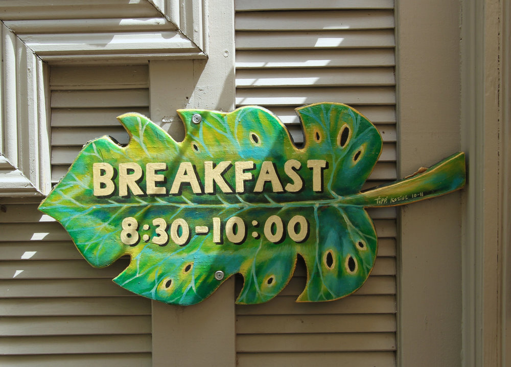 sign in the shape of palm frond. breakfast hours 8:30am to 10am.