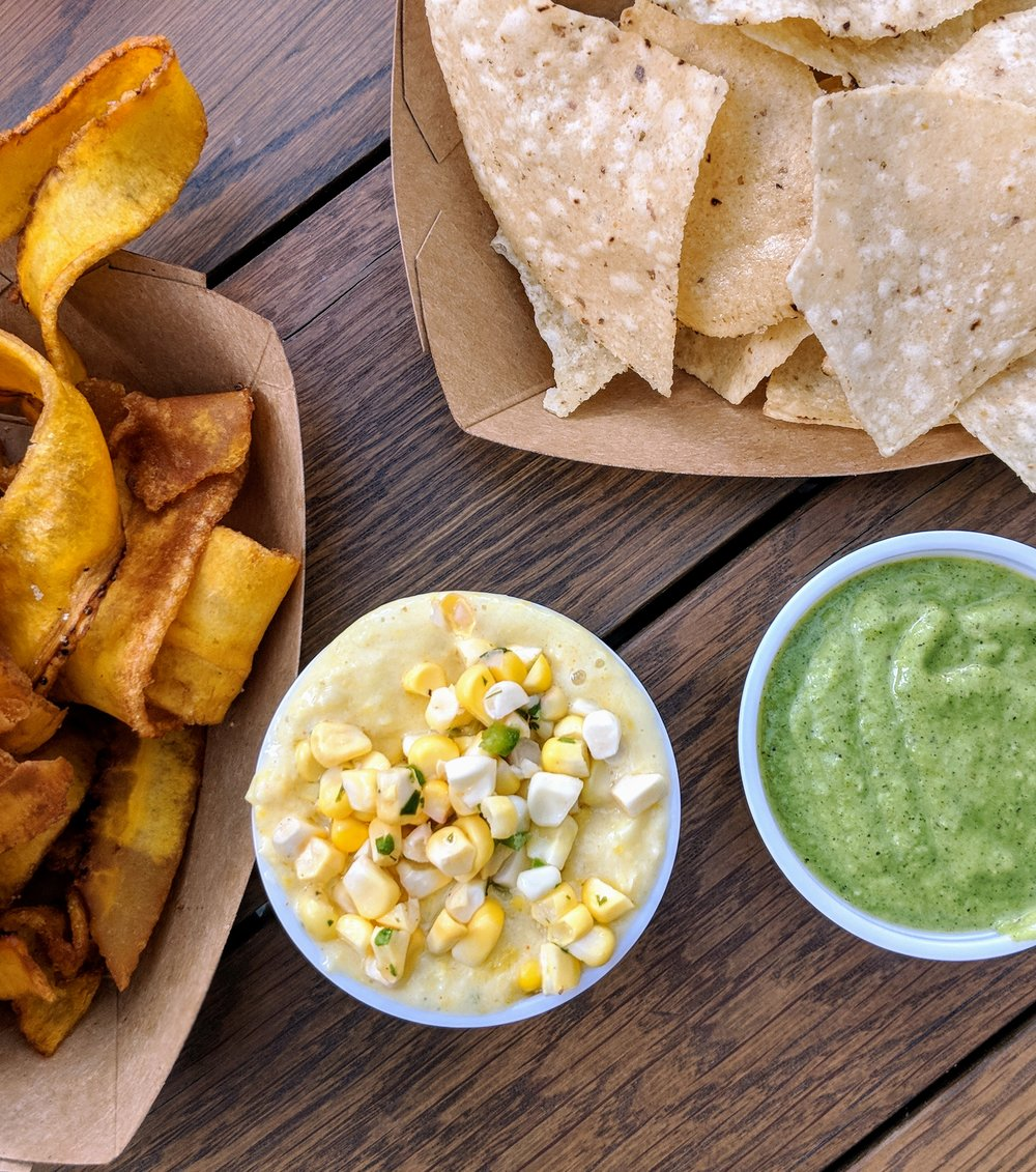 Fried lime salted plantain chips, street corn dip, yellow corn chips, and charred tomatillo and avocado dip