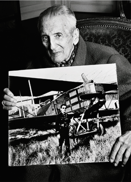 Djibrail NAZARE-AGA,aged 97, holding a photo of himself standing in front of a Breguet XIV plane when he was 17 years old
