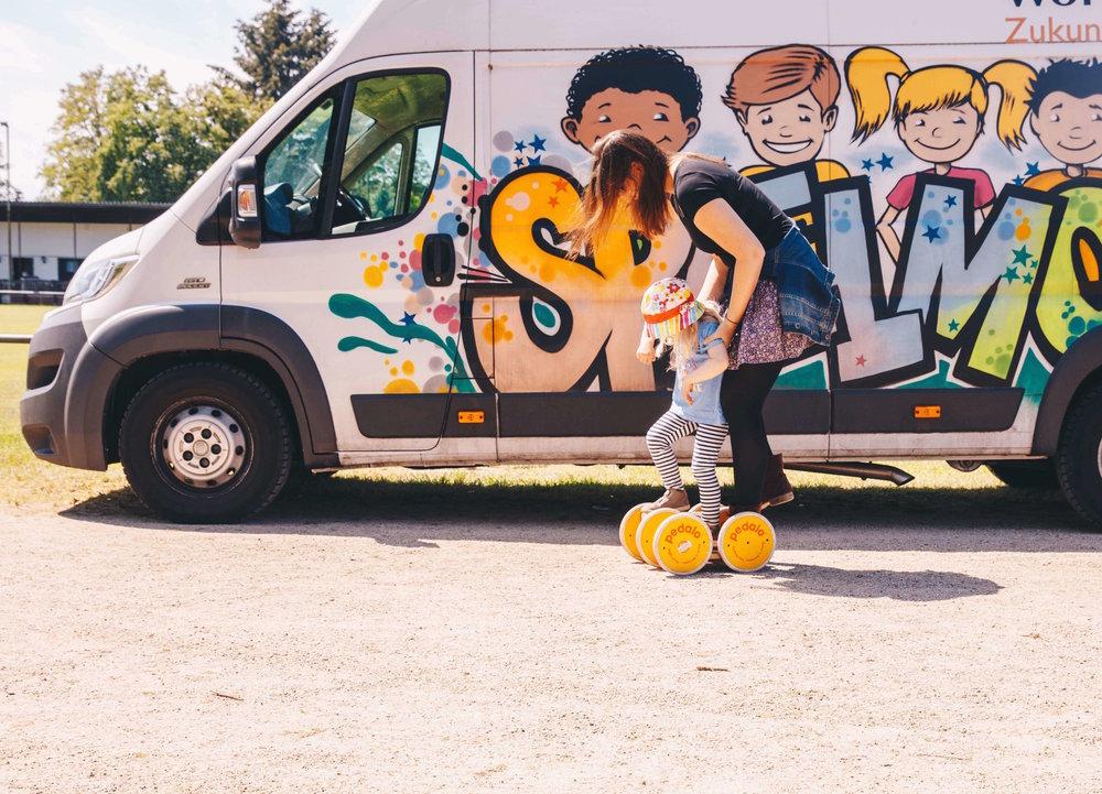 Spielmobil - Eine Flucht aus Krisenverhältnissen führt meist dazu, dass Kindern die Mitnahme von Spielzeug aus ihrem gewohnten Alltag nicht möglich ist, stattdessen haben sie meist schlimme Erfahrungen im Gepäck und wurden viel zu früh mit dem Ernst des Lebens konfrontiert. Das Spielen an sich rückt in den Hintergrund und sie müssen viel zu früh erwachsen sein. Diese Kinder brauchen einen Ort, an dem sie wieder Kinder sein können. Das Spielmobil schafft einen solchen Ort und fährt dafür jeden Tag in eine andere Unterkunft im Rhein-Main-Gebiet.