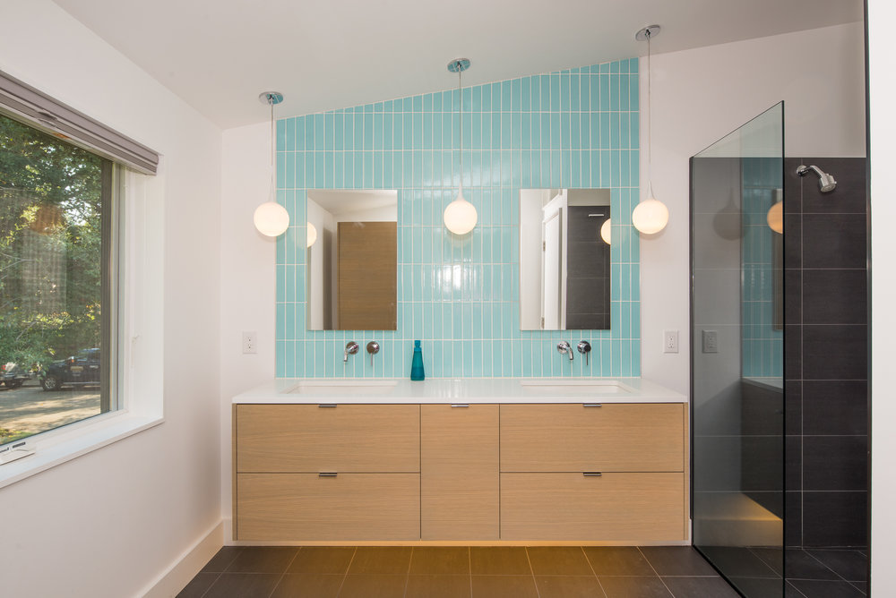 Floating wood bathroom vanity in front of blue subway tile wall