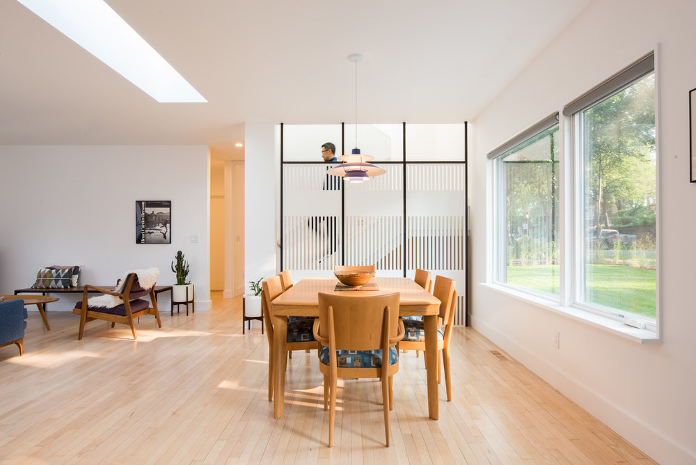 Mid-century dining room table in front of custom wood screen wall