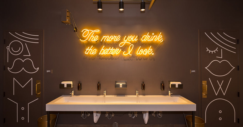 Custom neon sign in bathroom area of brewery remodel by Christian Dean Architecture.