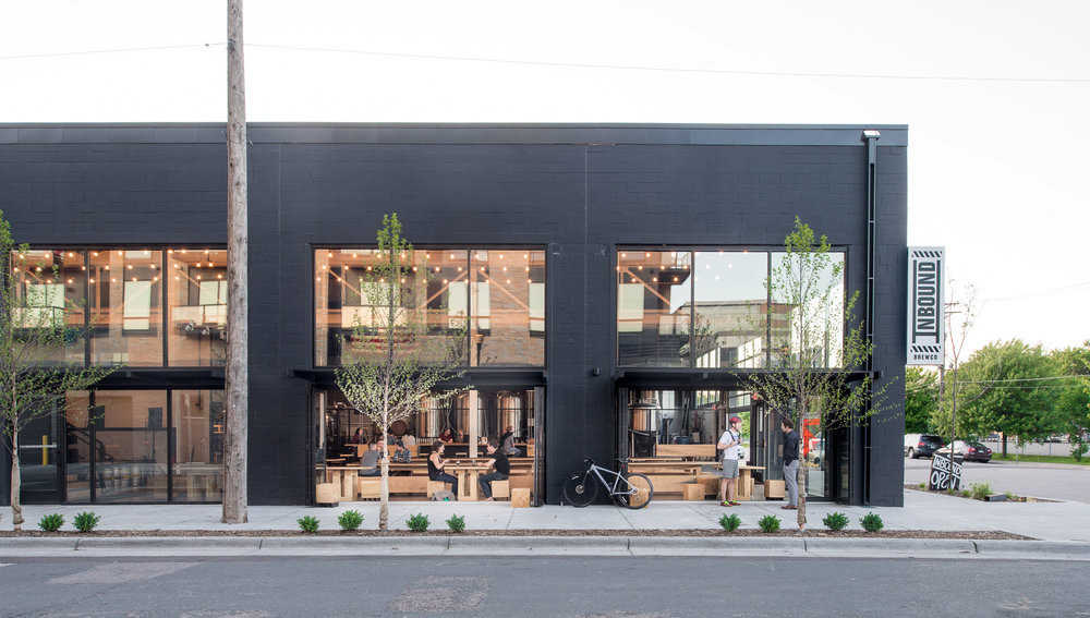 Black painted brewery space in Minneapolis with large windows and garage doors.