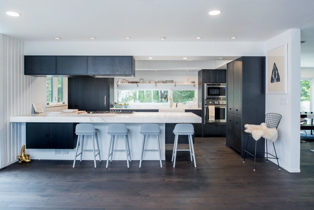 Modern kitchen renovation with black stained cabinetry and marble countertop